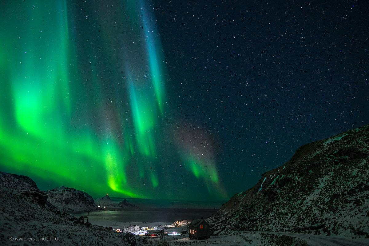 Unser Haus mit Polarlicht von der anderen Seite mit Bucht im Hintergrund